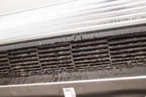Air conditioner prier to cleaning. The build-up of dust is quite evident.